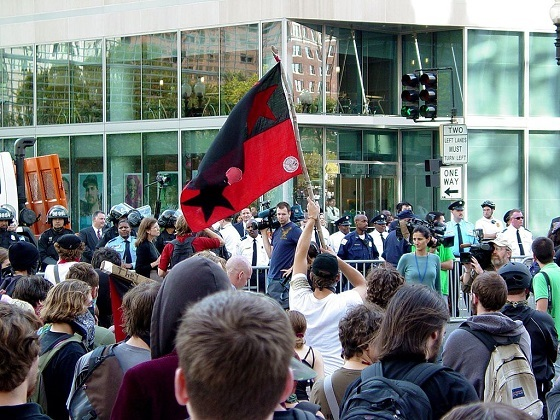 <i>A demonstrator waves a red and black flag during an intersection occupation outside the World Bank in Washington DC</i> (October 20, 2007). Wikimedia Commons