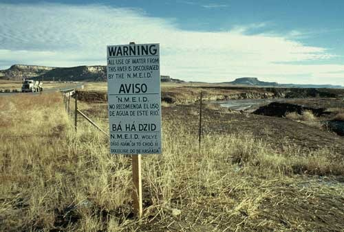 <i>A warning sign placed near the Puerco River by the New Mexico Environmental Improvement Division after the Church Rock Uranium Mill spill on July 16, 1979.</i> Photograph by the EPA / Wikimedia