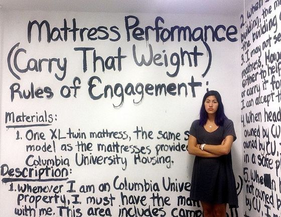 <i>Emma Sulkowicz with an exhibition of her work </i>Mattress Performance (Carry That Weight)<i>, 2014</i>. Photograph by Emma Sulkowicz / Wikimedia Commons