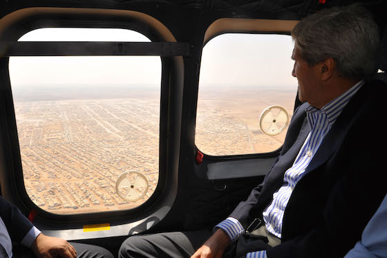 <i>US Secretary of State John Kerry views the Mrajeeb al-Fhood camp for Syrian refugees, 2014</i>. Photograph by US Department of State / Wikimedia Commons