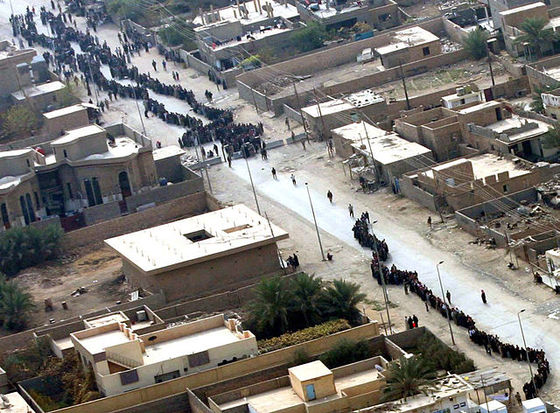 <i>Iraqis in the city of Husaybah wait in lines to vote, 2005</i>. Photograph courtesy of Wikimedia Commons