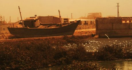 Photograph of shoreline, beached boats, in Porbandar, India
